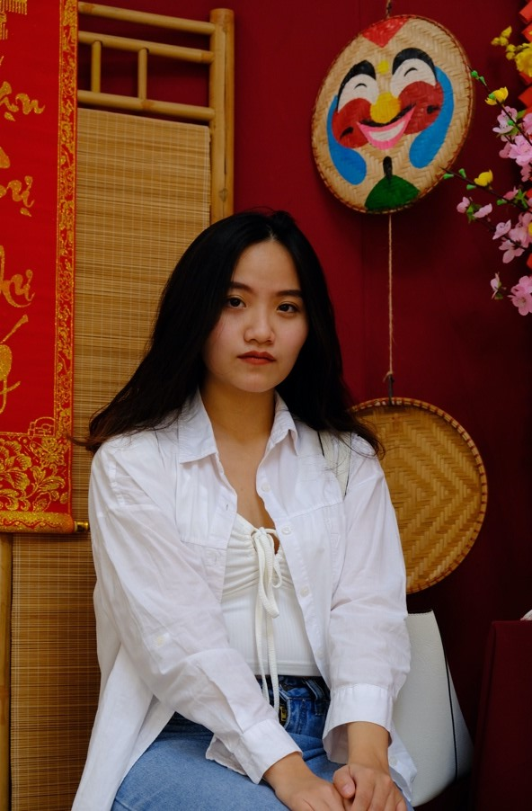 On the right is Khuê Ngô's recreation of the painting. She replicates Thuy's neutral face expression while wearing an open white blouse, a tank top, and blue high-waisted jeans. Her black hair falls down her shoulders and her hands are laid on her knees. Her back is straighter than Thuy's and she sits high on her hips. The background is vibrant red with some cherry blossoms peeking in from one corner. There are two Vietnamese bamboo masks on the wall as decoration as well as a bamboo room divider screen.