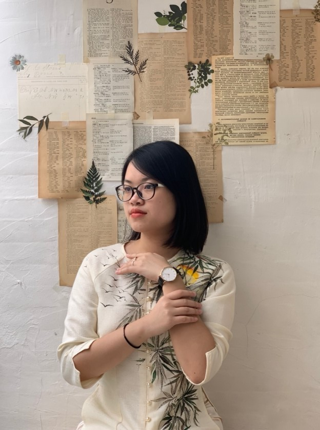 On the right is Sam Lien's recreation of her own great uncle's painting. Her posture remains the same as the painting, but she is sporting a men's wristwatch and a modernized version of the áo dài with green leaves on the left half. The background white bricks with coffee-colored papers and green leaves matching Sam's áo dài.