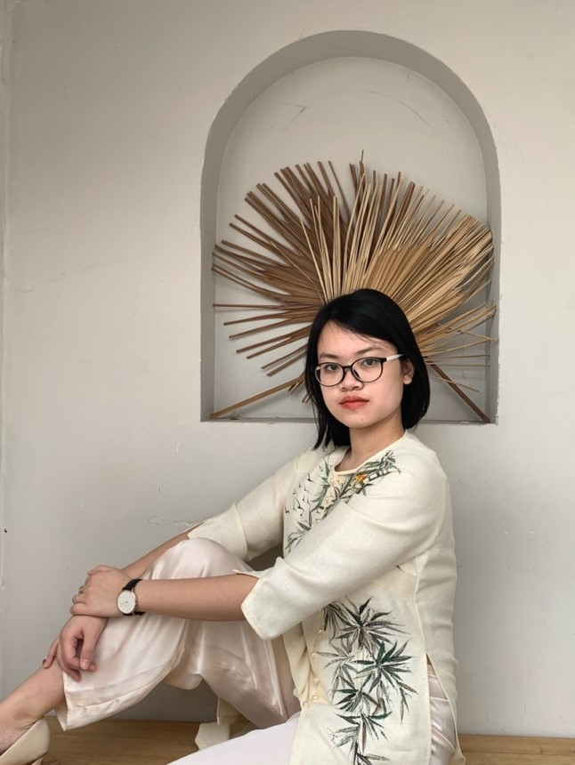 On the right is Sam Lien's recreation of the painting of her great uncle. Her short hair matches the painting. She sits with her right leg raised onto the bench, showing off the silk pants of the áo dài and her men's wristwatch. Her background is plain with cream colored with two leaf fans as decoration. Sam positions her head right in front of the fans to create an illusion of a crown or Vietnamese mấn (headress).