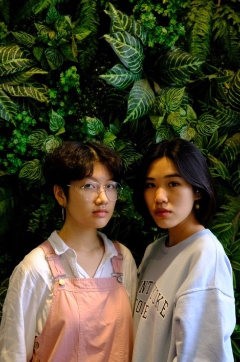 On the right are Ren and Thiên An's recreation of the painting. Ren (left) is wearing a white blouse, pastel pink dress, and big prescription glasses. Their hair is short and curly. Thiên An (right) is wearing a Mount Holyoke pastel blue sweatshirt. Her hair is longer than Ren and reaches just below her ears. She is turning her body sideway toward Ren's. Both individuals are looking at the camera.