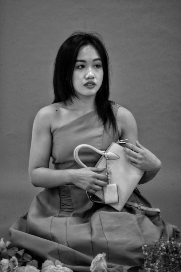 Kim's recreation of the women in blue is also in black and white. There are two versions of it. Both depict Kim holding her expensive white Prada bag, with her fingers grazing the surface as if playing an instrument with strings. The version on the left depicts Kim with hair untied while wearing a one shoulder dress. She is holding a small white handbag in a pool of flowers around her. She is looking far off to the right side of the photo and her lips are slightly apart. The second version depicts Kim in a spaghetti strap dress. Her hair is loosely tied behind her head. Her bare left leg is pushed forward while her right one curls to a side below the knee. She is still holding the handbag. Her well-trained right arm is on display.