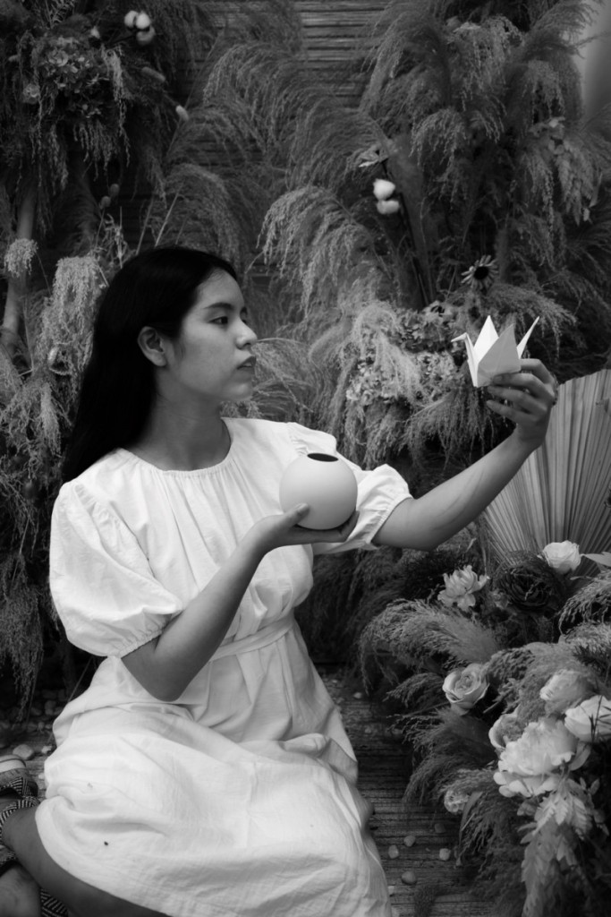Below is Nhật Anh's recreation of the painting in black and white. Nhật Anh switches the traditional áo dài for a simple white puffy-sleeved dress. She is sitting on her legs while holding a small circular vase in her right hand. Instead of a real bird in a cage, Nhật Anh is holding a white paper crane in her left hand and gazing upon it.
