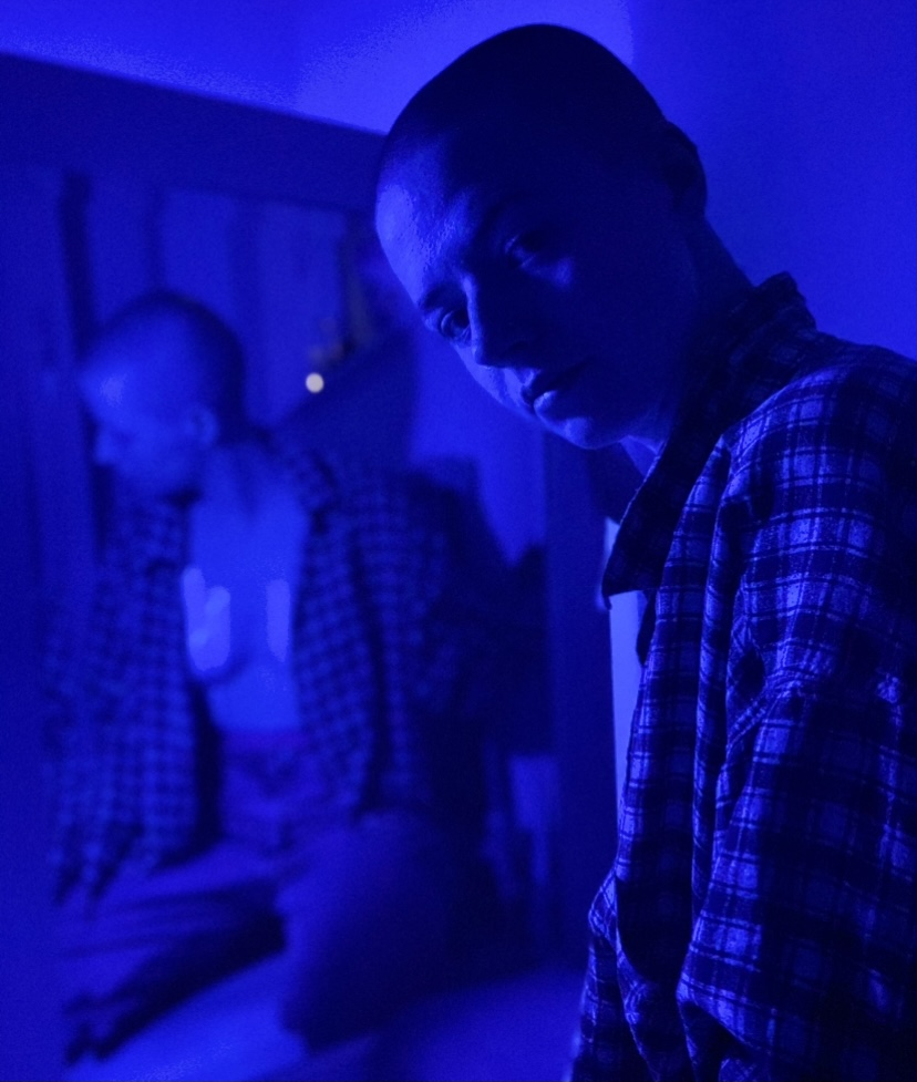 Izzy is sitting on the floor of their house on their knees under a heavy blue lighting. They wearing a checkered shirt and jeans are facing a mirror that is propped up in front of them, knees apart and looking over their shoulder at the camera lens. In the reflection of the mirror, Izzy's shirt hands open to reveal their breasts are taped down. Their face is sad and disturbed.