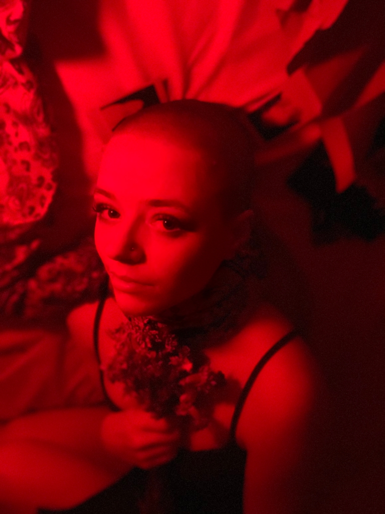 Izzy is laid down in a nest of fabric in the fetal position wearing a small green dress and heavy makeup, head rotated and looking up toward the lens. The scene is under a deep red lighting and they are clutching dead flowers to their chest while laid among old photographs and fabric that is secured to their neck. Izzy's face is fearful yet accusative as they stare at the viewer.